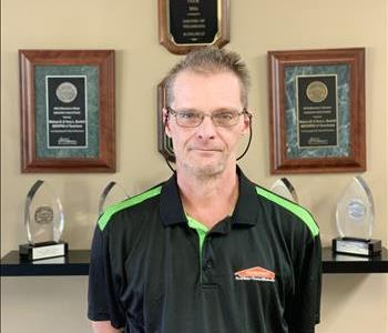 A SERVPRO employee taking a picture in front of awards to update the employee photos
