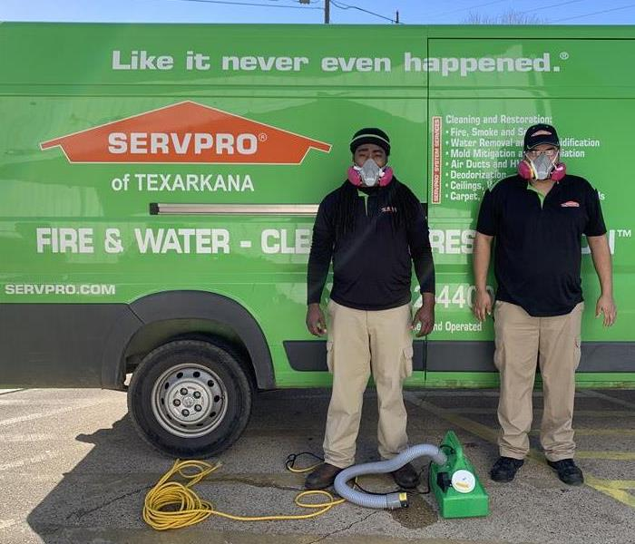 SERVPRO employees standing infront of a van with respirators
