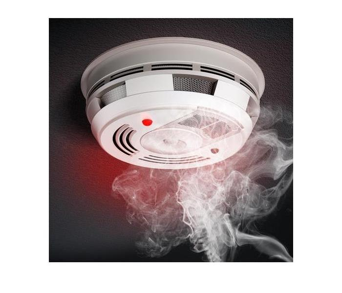 smoke alarm with smoke going up to it